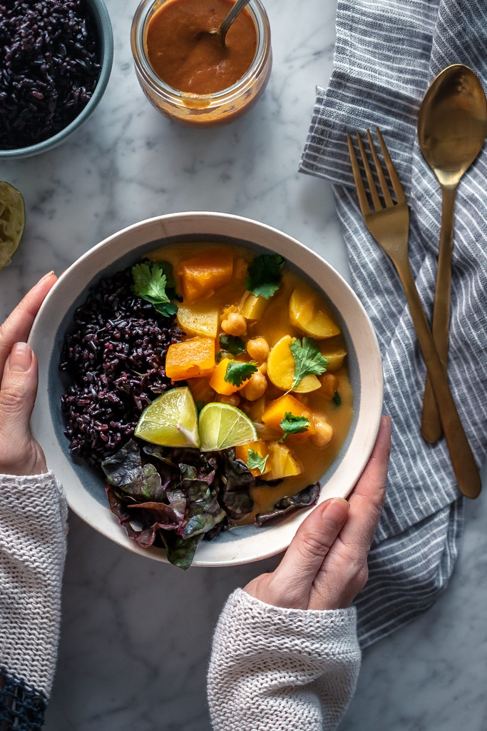 two hands holding a bowl of Yellow Thai Butternut Squash Curry and black rice
