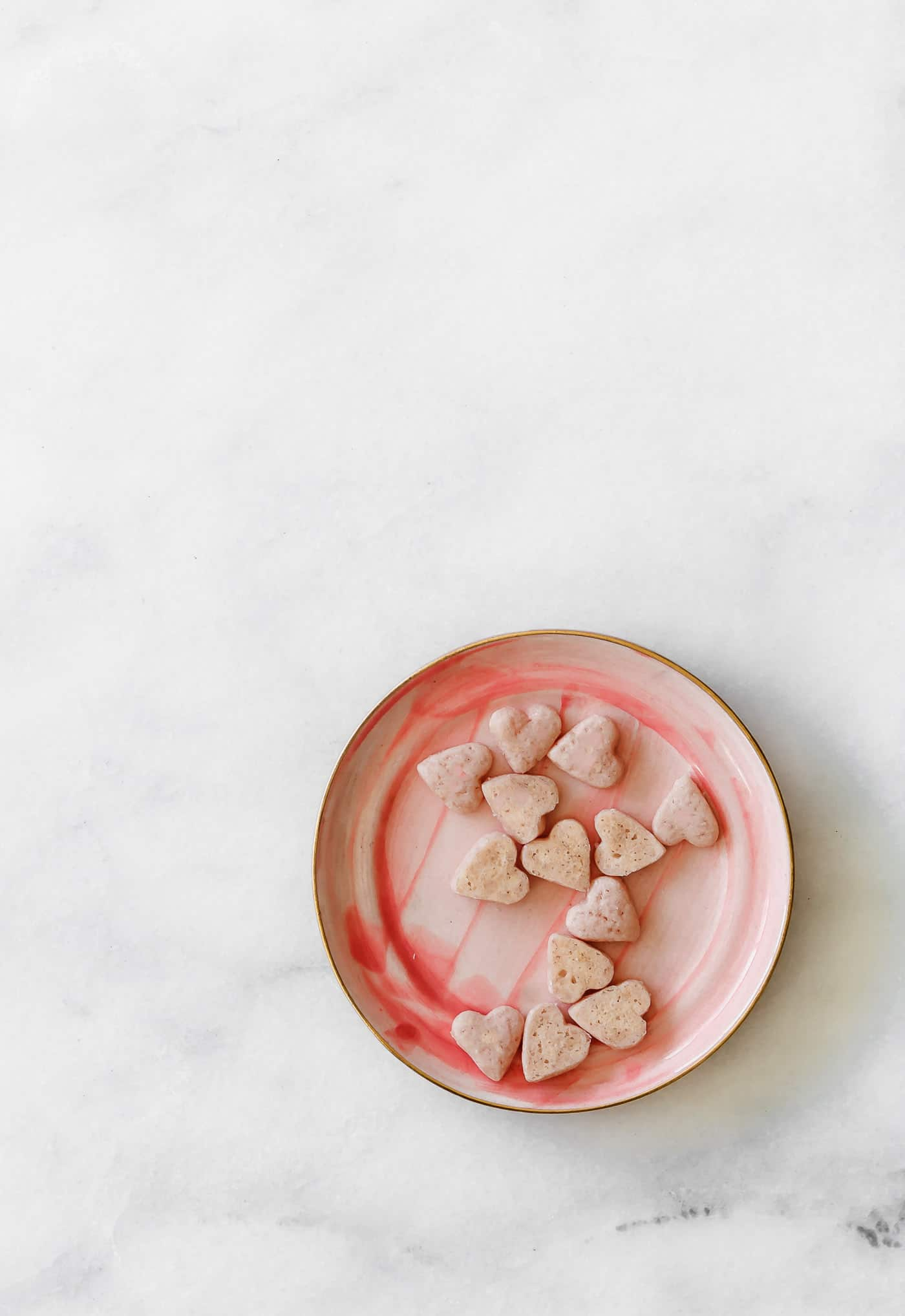 tiny pink heart cookies on a pink plate