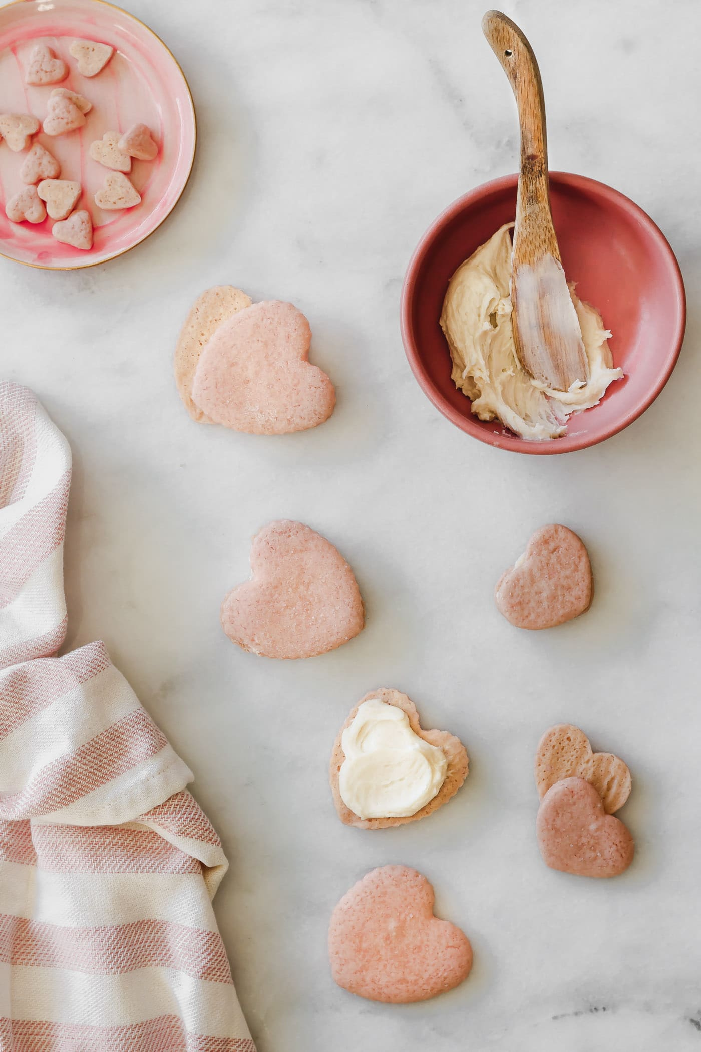 Heart Shaped Sandwich Cookies being filled with frosting