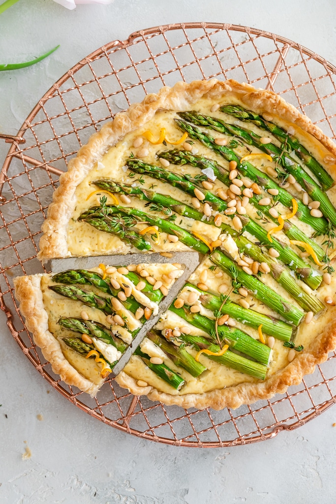 Puff Pastry Asparagus Tart with as slice removed on a copper cooling rack