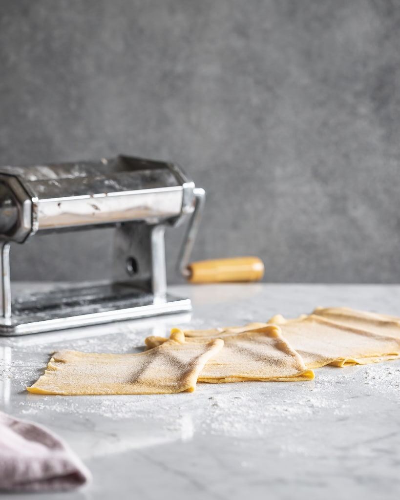 sheets of homemade pasta dough next to a pasta roller