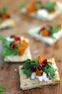 Individual Roasted Sweet Potato Flatbreads with ricotta and pomegranate served on a wooden board