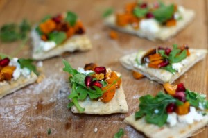 Roasted Sweet Potato Ricotta Flatbread with pomegranate seeds and arugula served on a wooden board