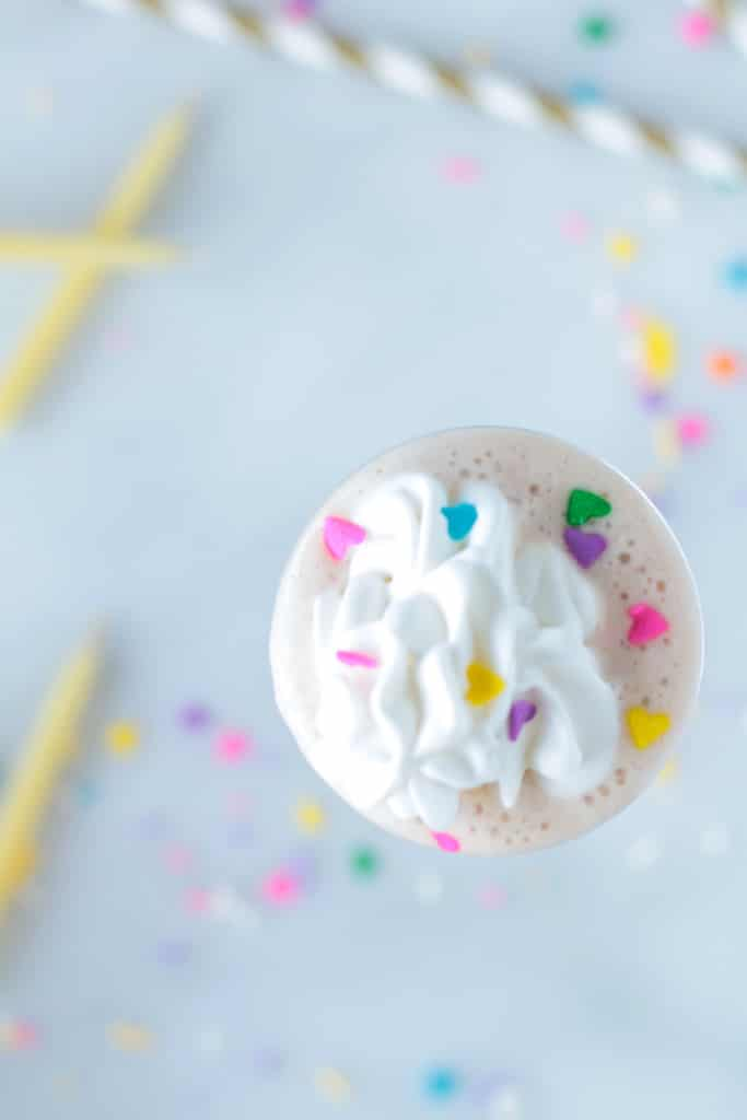 overhead shot of a Healthy Vegan Birthday Cake Protein Shake with rainbow sprinkles