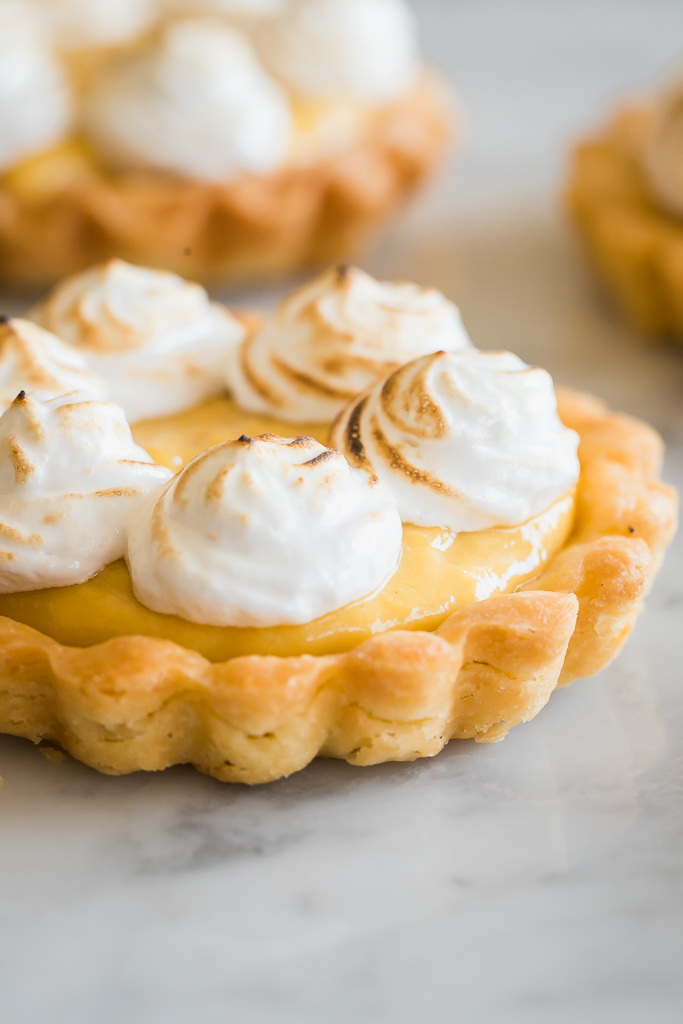 close up of a mini mango curd tartlet with toasted mini meringue swirls
