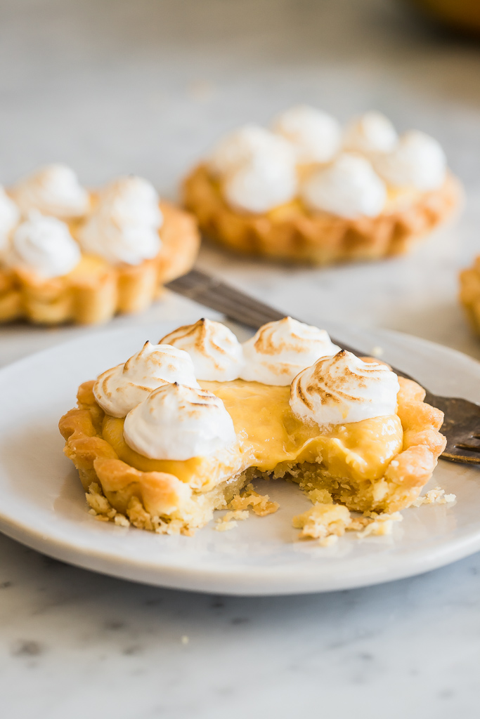 close up side view of a mini mango curd tartlet with toasted meringue