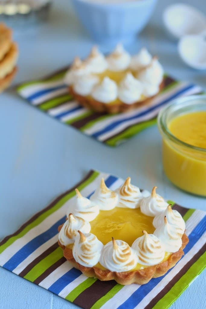 side view of a mini mango tartlet  with piped toasted meringue around the edges