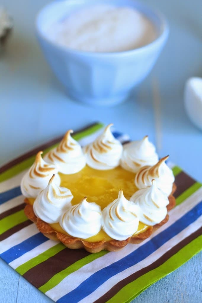close-up of a homemade mango curd meringue mini tartlet on a striped napkin with whipped egg whites in the back