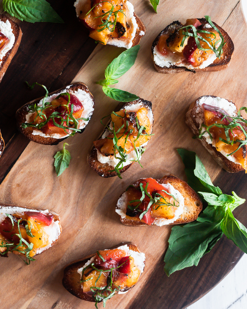 bite sized grilled peach bruschetta with goat cheese and fresh basil on a wooden board