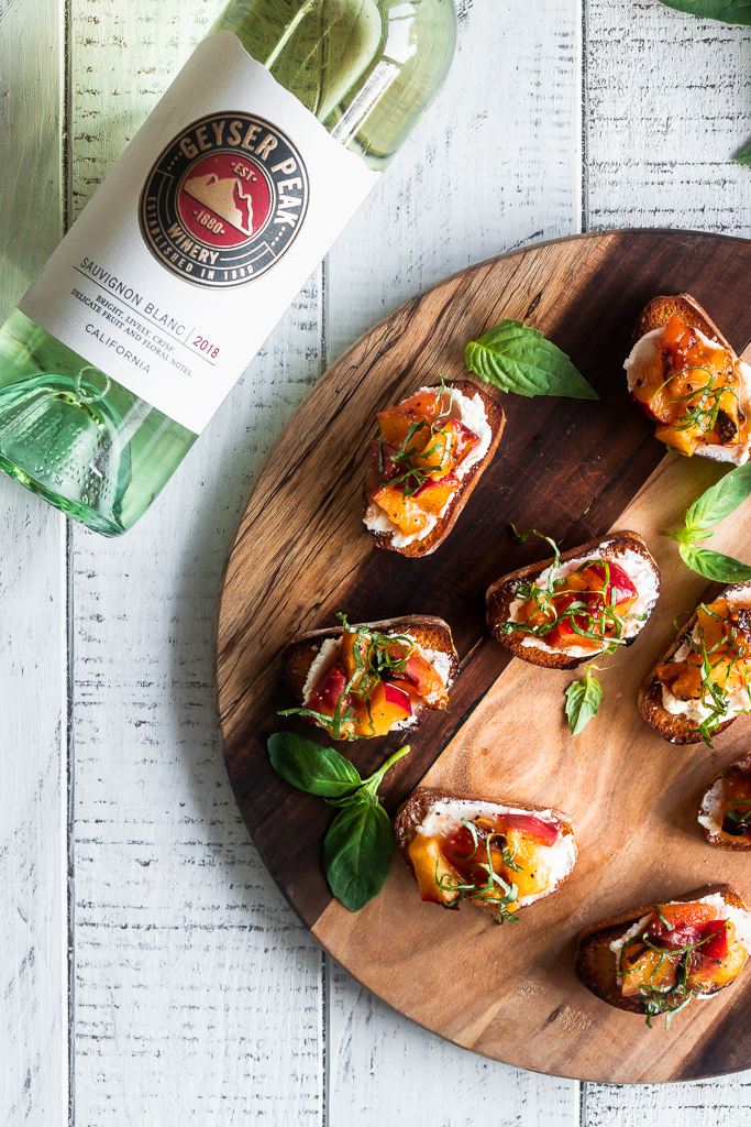 grilled peach bruschetta served on a wooden board next to a bottle of white wine