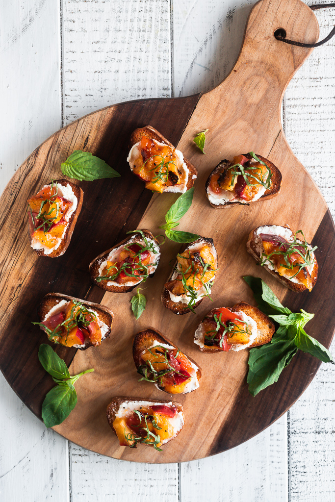 grilled peach bruschetta with basil on a round wood serving boars