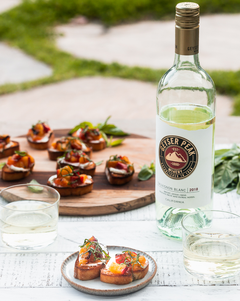 Grilled Peach Bruschetta served on a small plate with a platter of bruschetta and white wine in the background