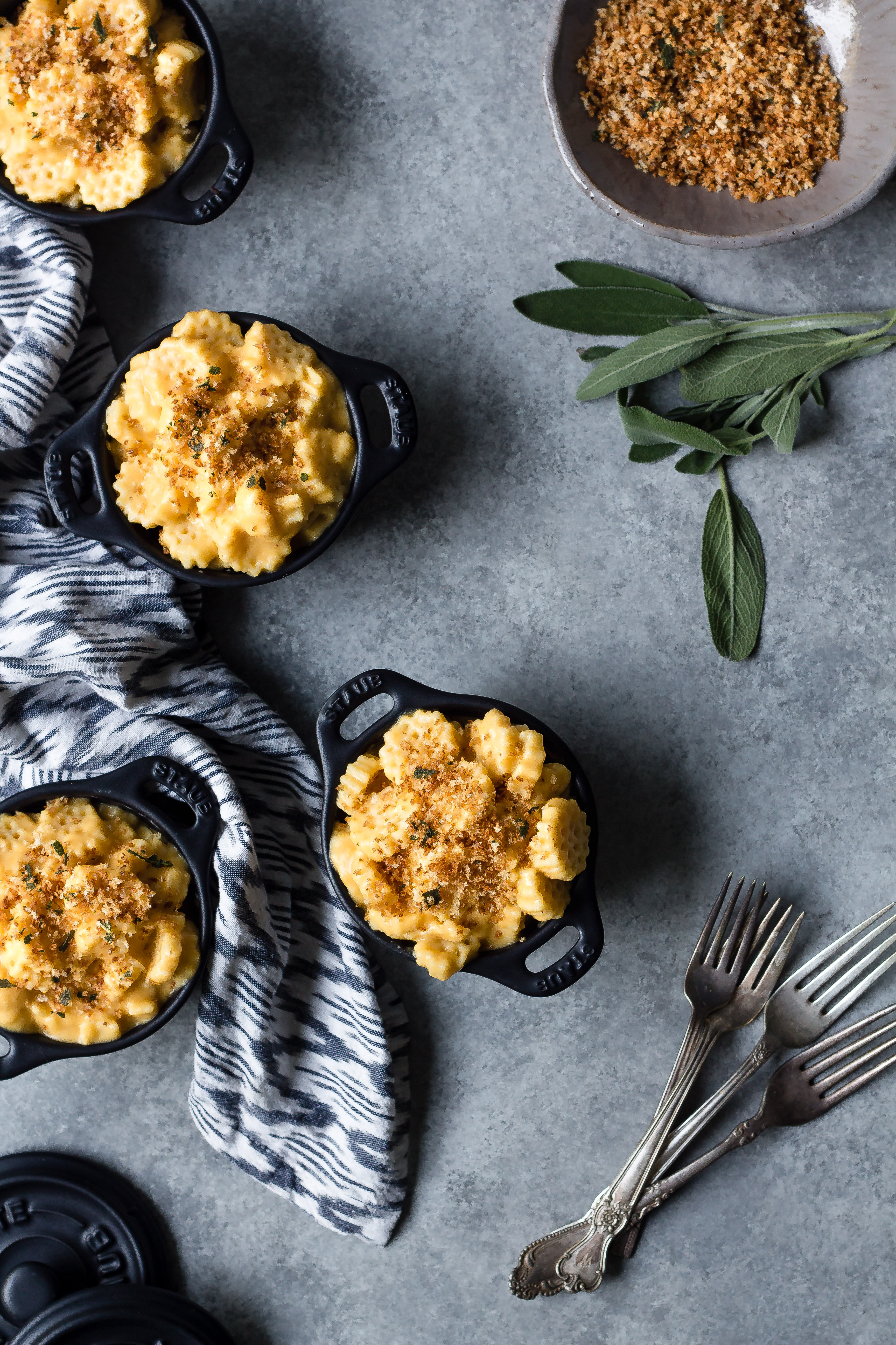 four mini crocks of vegan butternut squash mac and cheese in crock with breadcrumbs and sage
