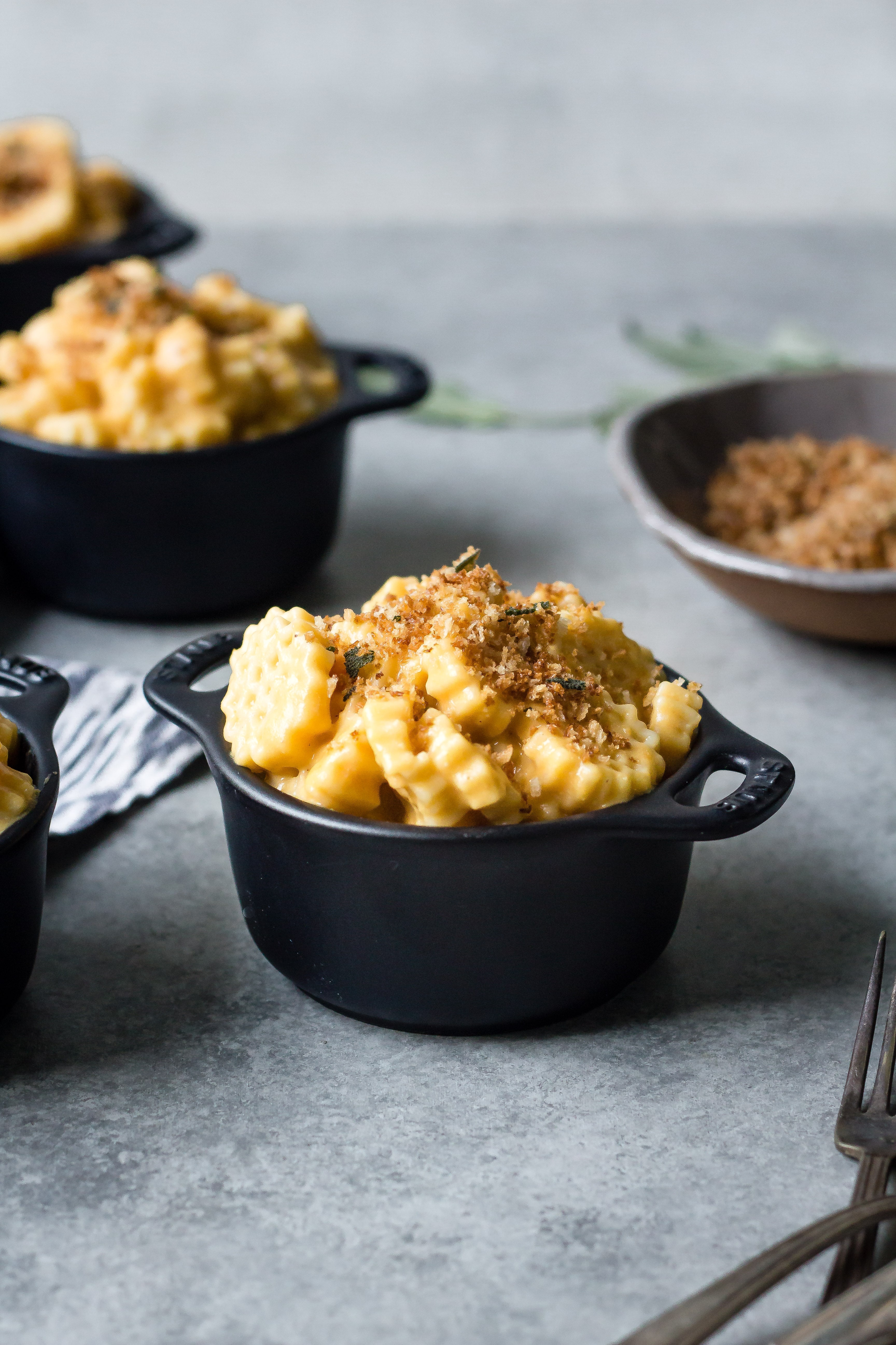 vegan butternut squash mac and cheese in crock with breadcrumbs and sage