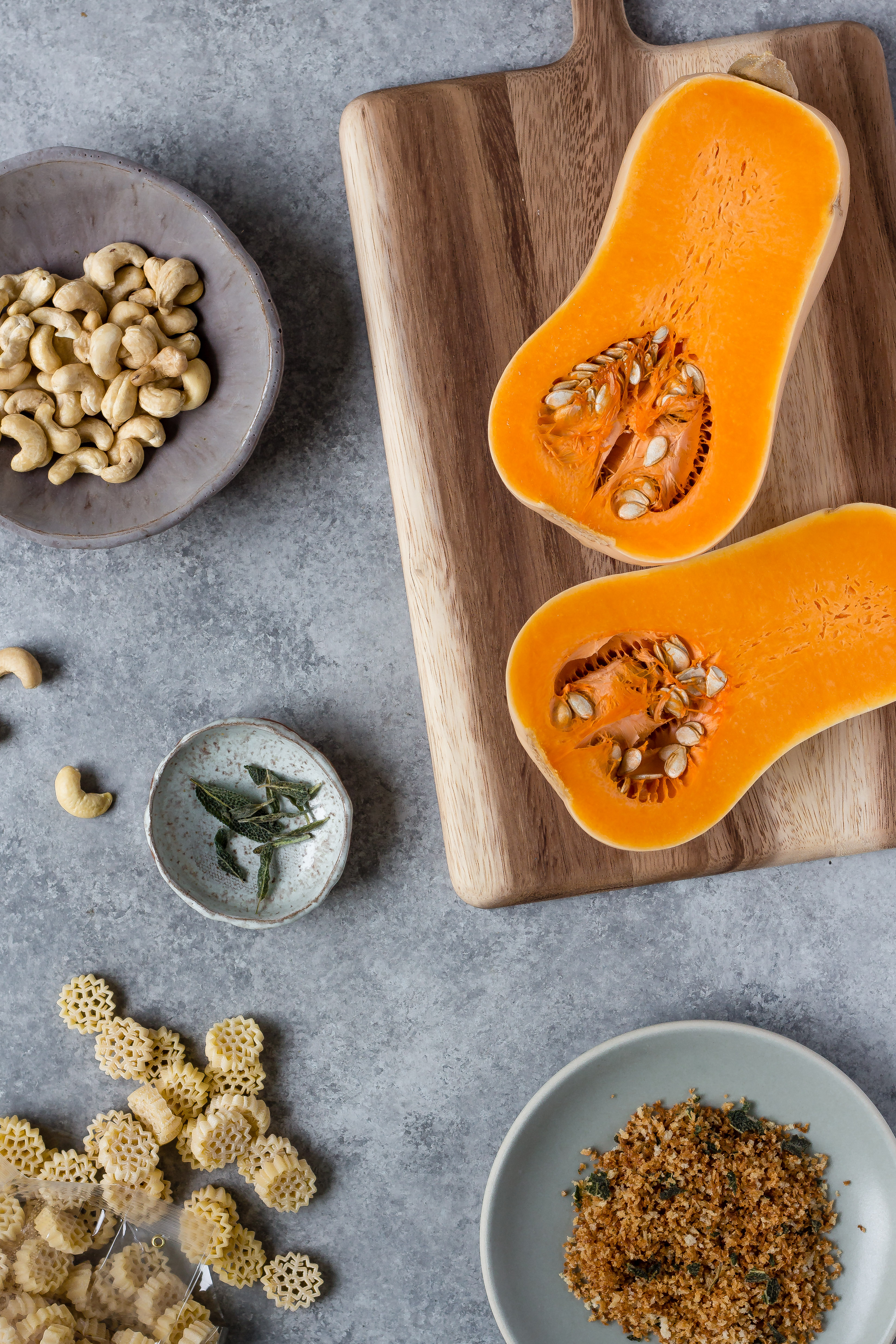 ingredients for vegan butternut squash mac and cheese- sage, cashews, pasta, breadcrumbs, butternut squash