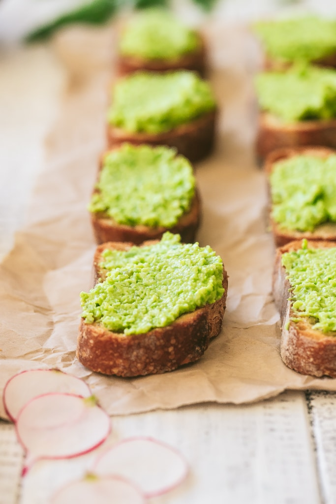 side view of homemade vegan crostini topped with pea pesto