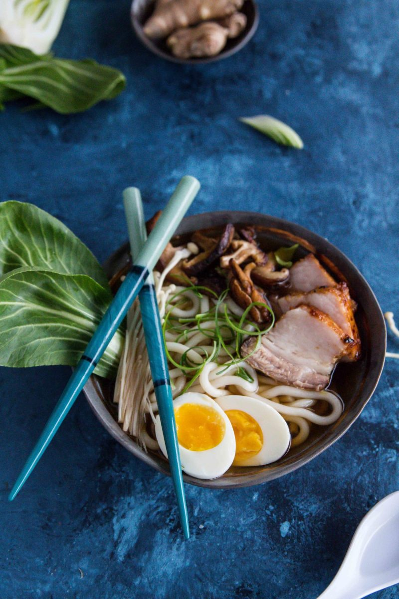 a bowl of Pork Belly Udon Noodle Soup topped with a halved boiled egg and mushrooms, with chopsticks on the side