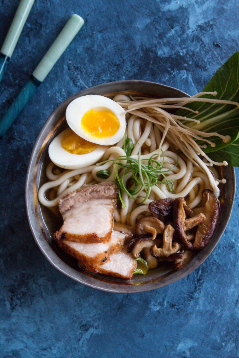 a bowl of Pork Belly Udon Noodle Soup topped with Asian mushrooms and a soft boiled egg