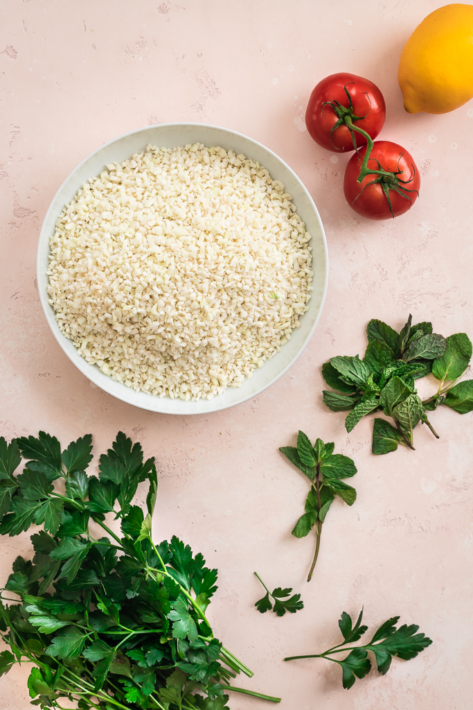 bowl of cauliflower rice with mint and parsley bunches