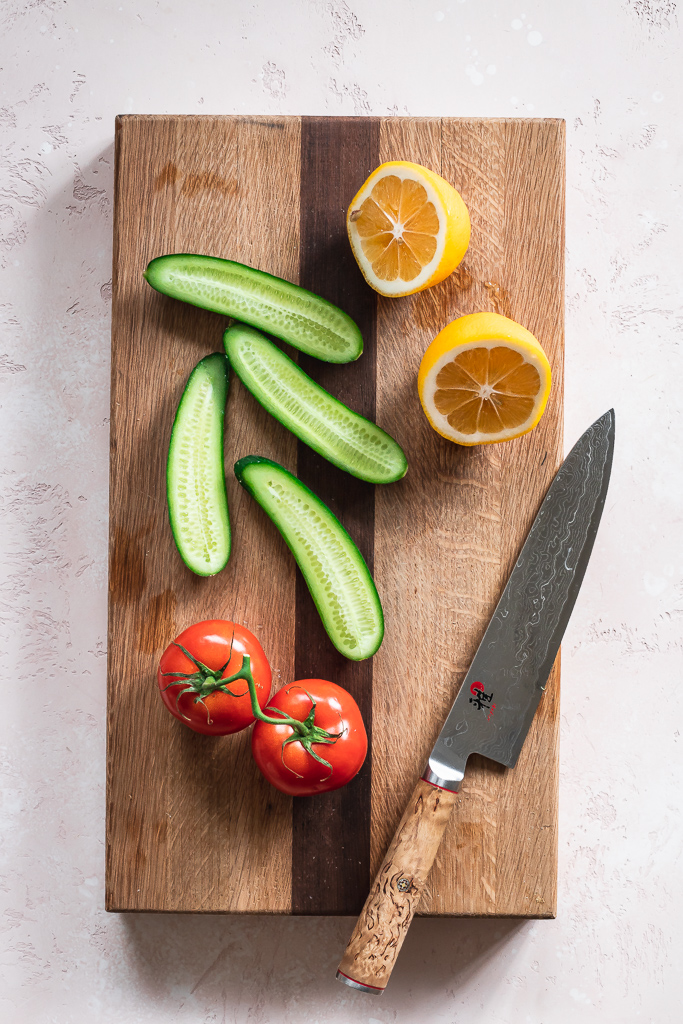 lemon, cucumber and tomato on a cutting board