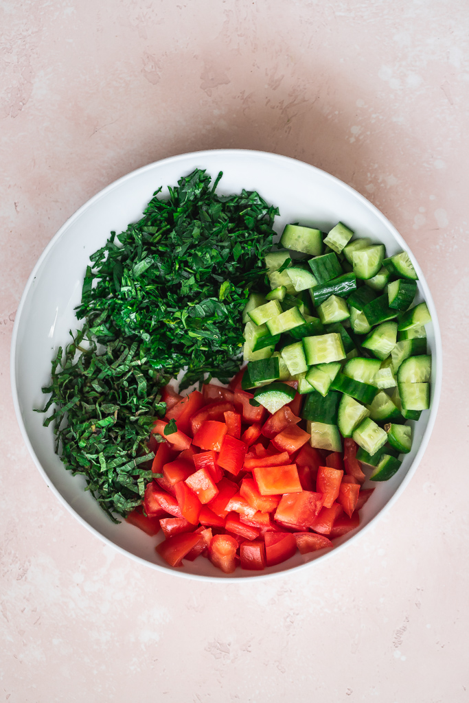 bowl of diced tomato, diced cucumber and chopped herbs