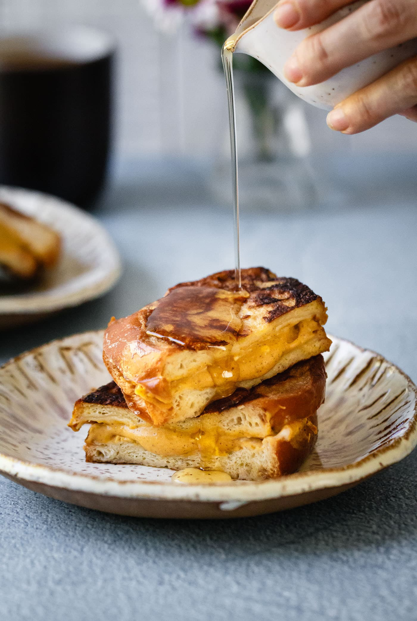 maple syrup being poured on top of Pumpkin Cheesecake Stuffed French Toast