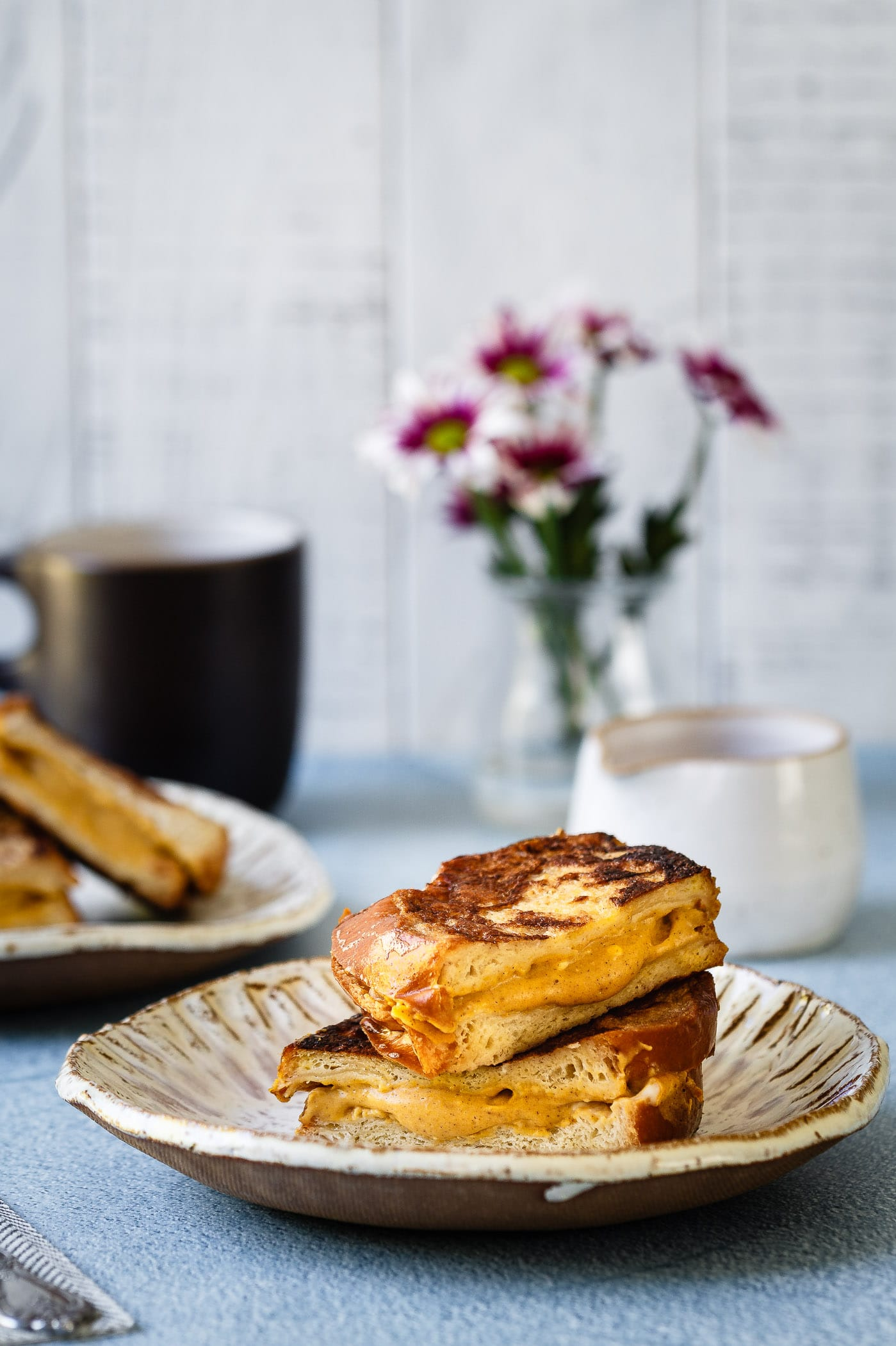 two stacked pieces of Pumpkin Cheesecake Stuffed French Toast with cheesecake filling oozing out the center