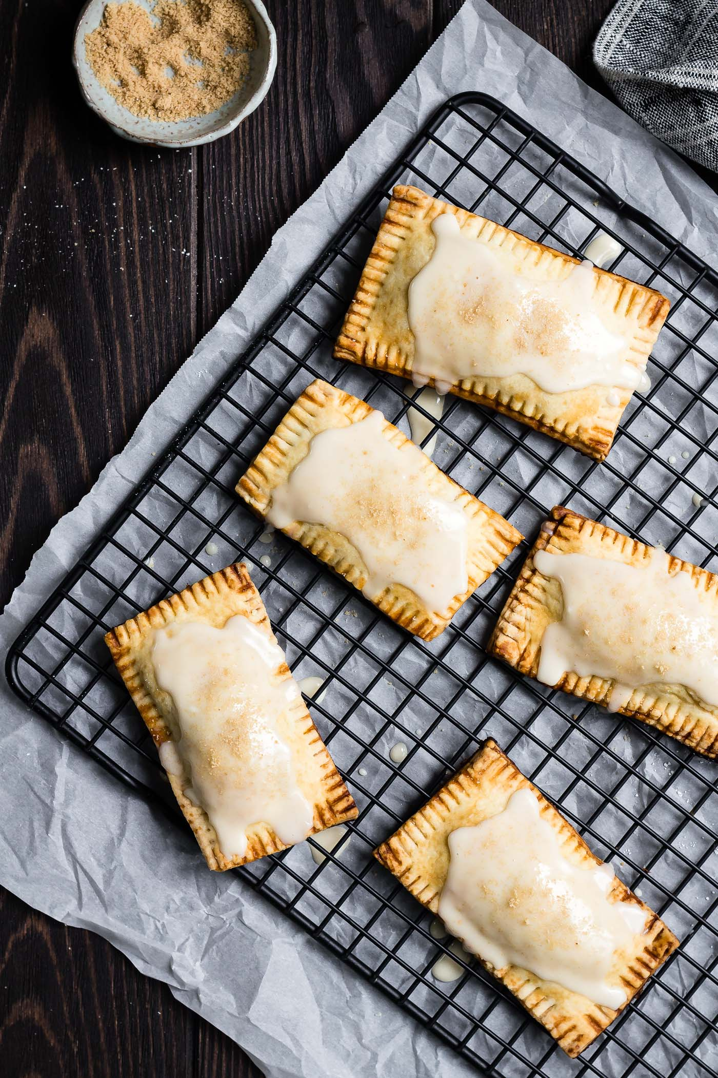 vegan maple pumpkin pop tarts with maple glaze on a black cooling rack