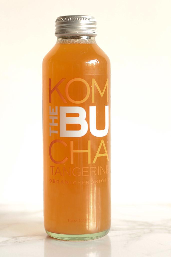 a bottle of tangerine kombucha against white surface
