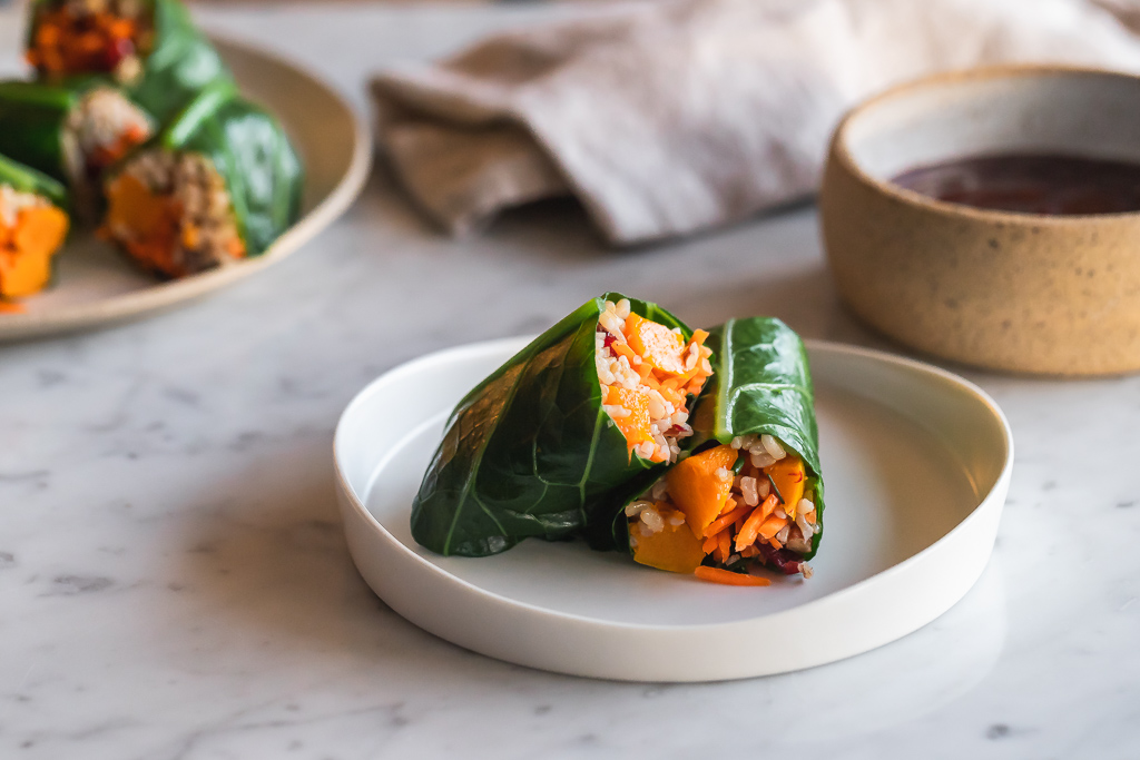 brown rice and autumn vegetable collard green roll on a plate