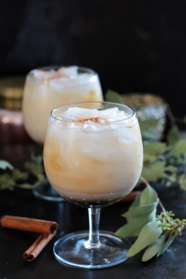 Horchata White Russian served in two cocktail glasses with cinnamon bark on the side