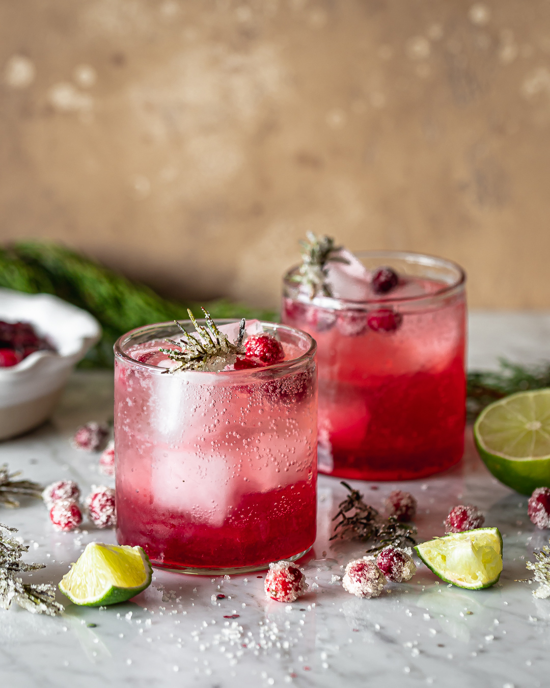 side view of two lowball glasses with cranberry smash cocktails garnished with fresh cranberries and rosemary twigs