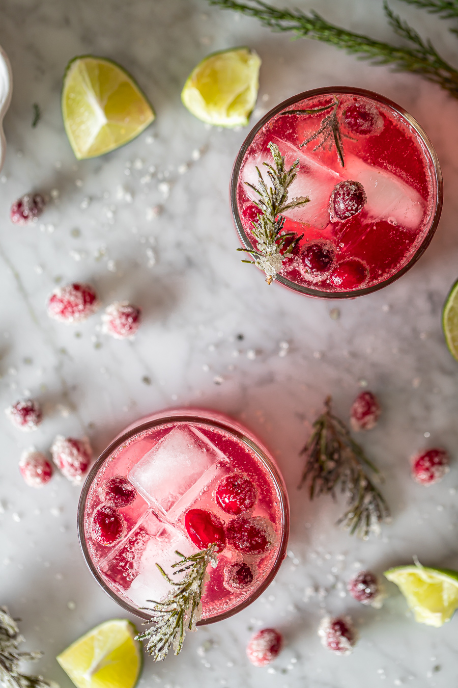overhead shot of two cranberry smash cocktails with sugared cranberries, sugared rosemary and lime