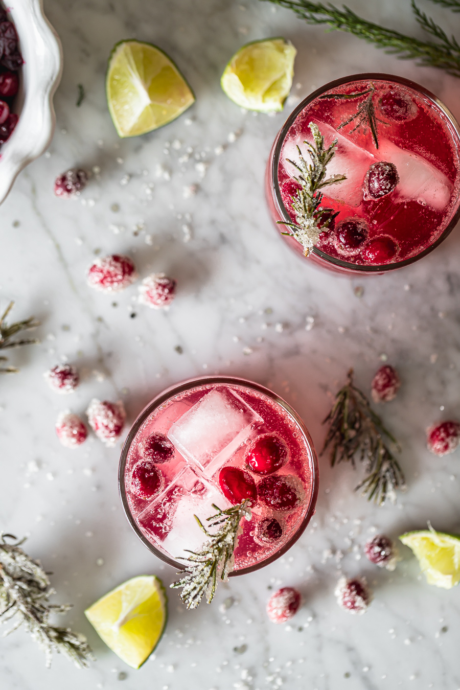 overhead shot of two glasses of cranberry smash cocktail made with gin, cranberry sauce and rosemary simple syrup
