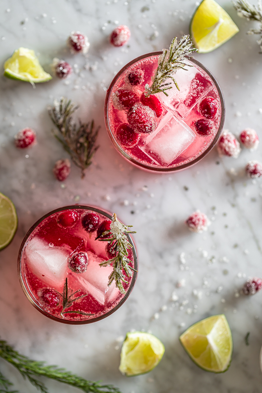 overhead shot of two lowball glasses with cranberry smash cocktail with sugared cranberries, sugared rosemary and lime
