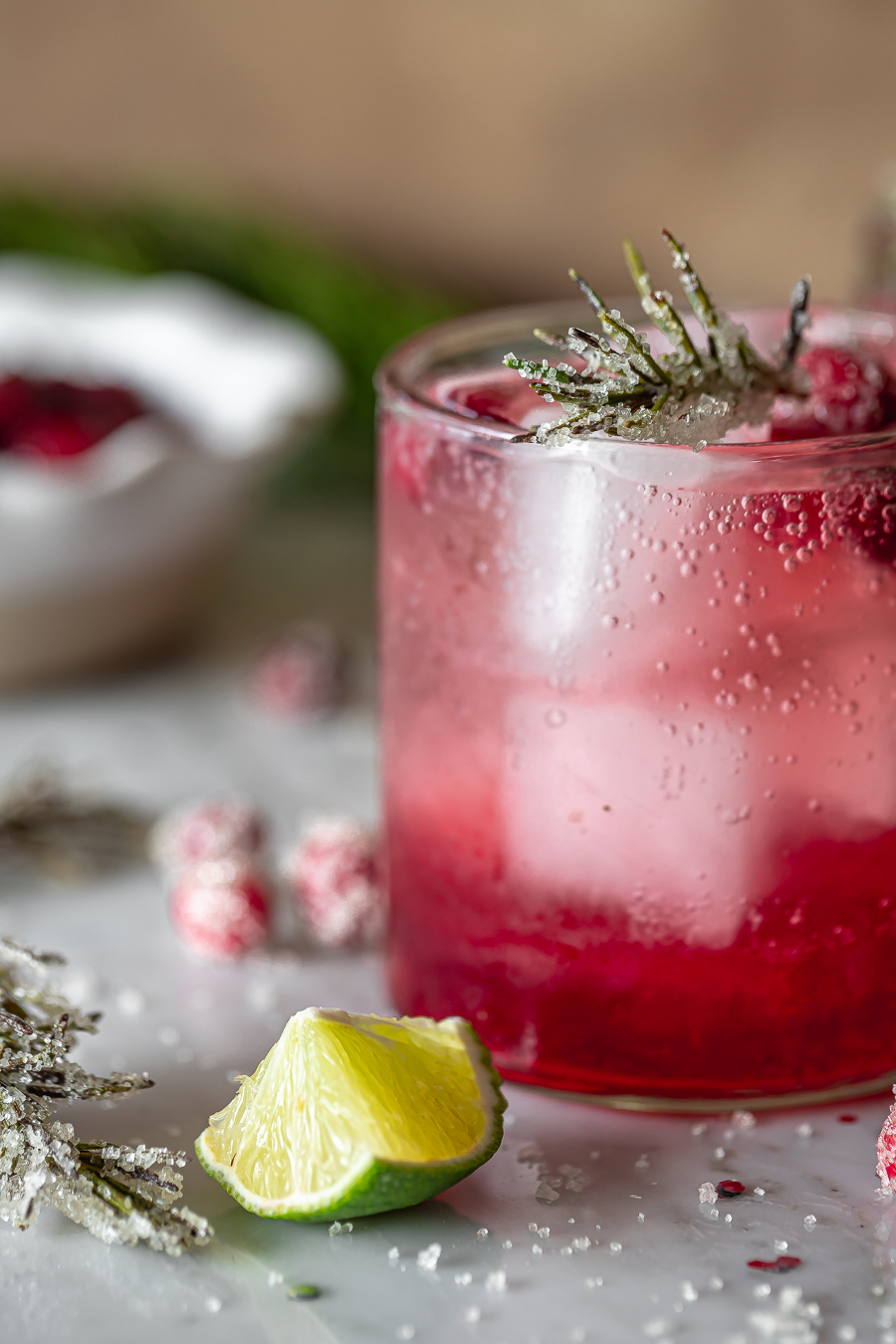 side view of a fresh cranberry gin cocktail served on the rocks with a lime slice and rosemary twig on the side