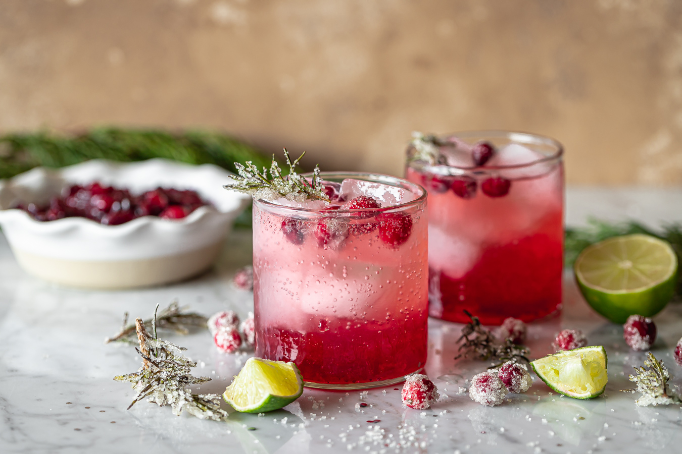 side view of two glasses of cranberry smash holiday cocktails made with leftover cranberry sauce and gin with lime wedges and rosemary on the side