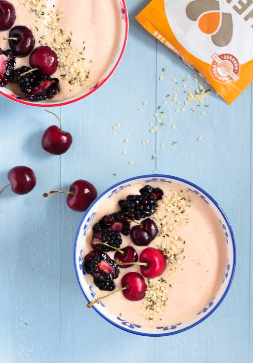overhead shot of two peanut butter and jelly smoothie bowls topped with fresh cherries and hemp seeds