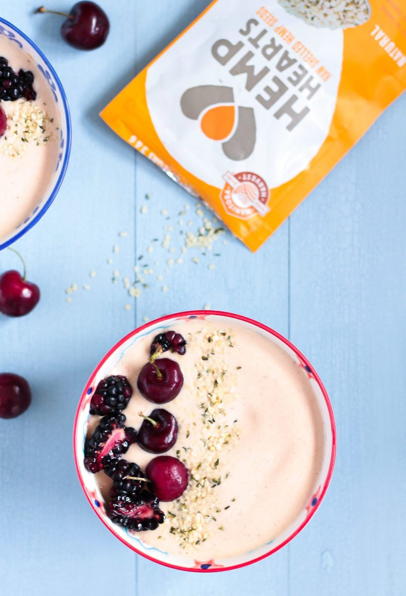 Peanut Butter & Jelly Smoothie Bowl with help seeds, blackberries and cherries on a pale blue wooden surface