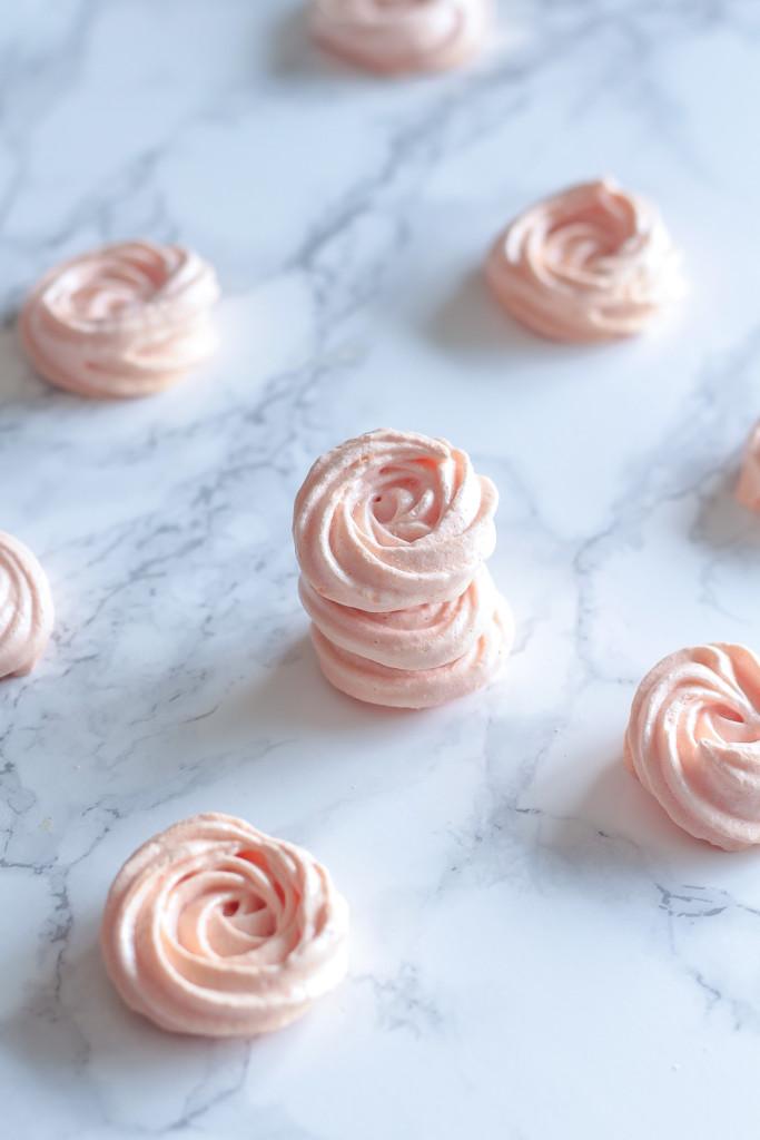 pastel pink Rose Meringue Cookies on a marble countertop