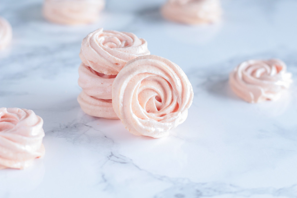 Rose Meringues stacked on a marble countertop