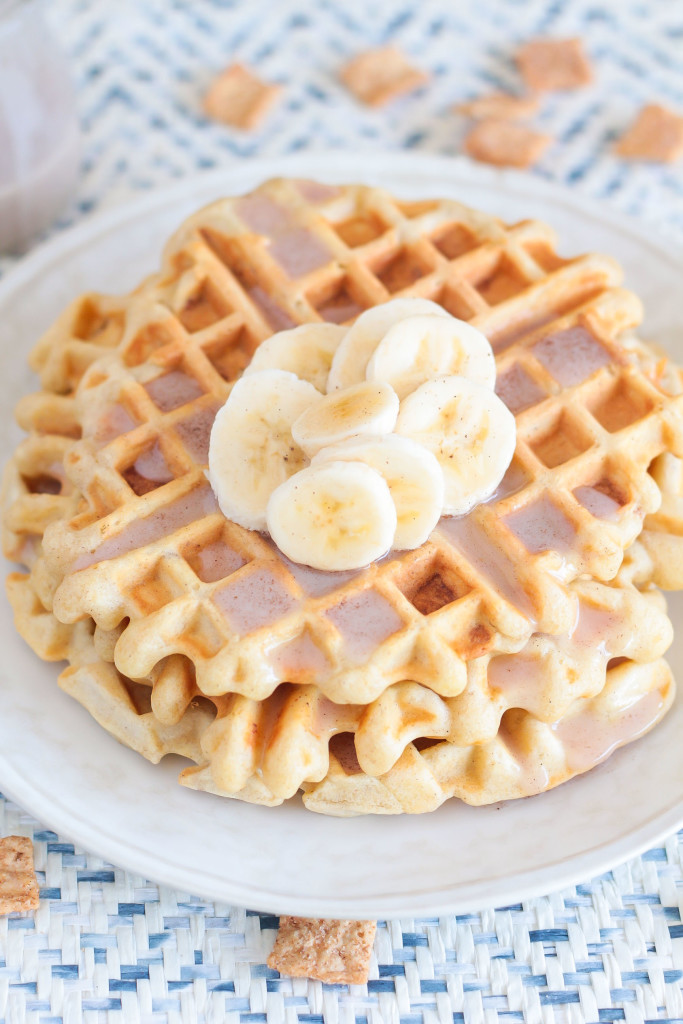 close-up of a plate of Cinnamon Toast Crunch Waffles with cereal milk glaze and banana slices on top