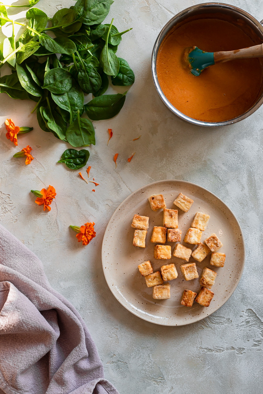 crispy pan-fried tofu cubes on a plate with a bowl of Thai peanut sauce and a pile of spinach leaves in the background