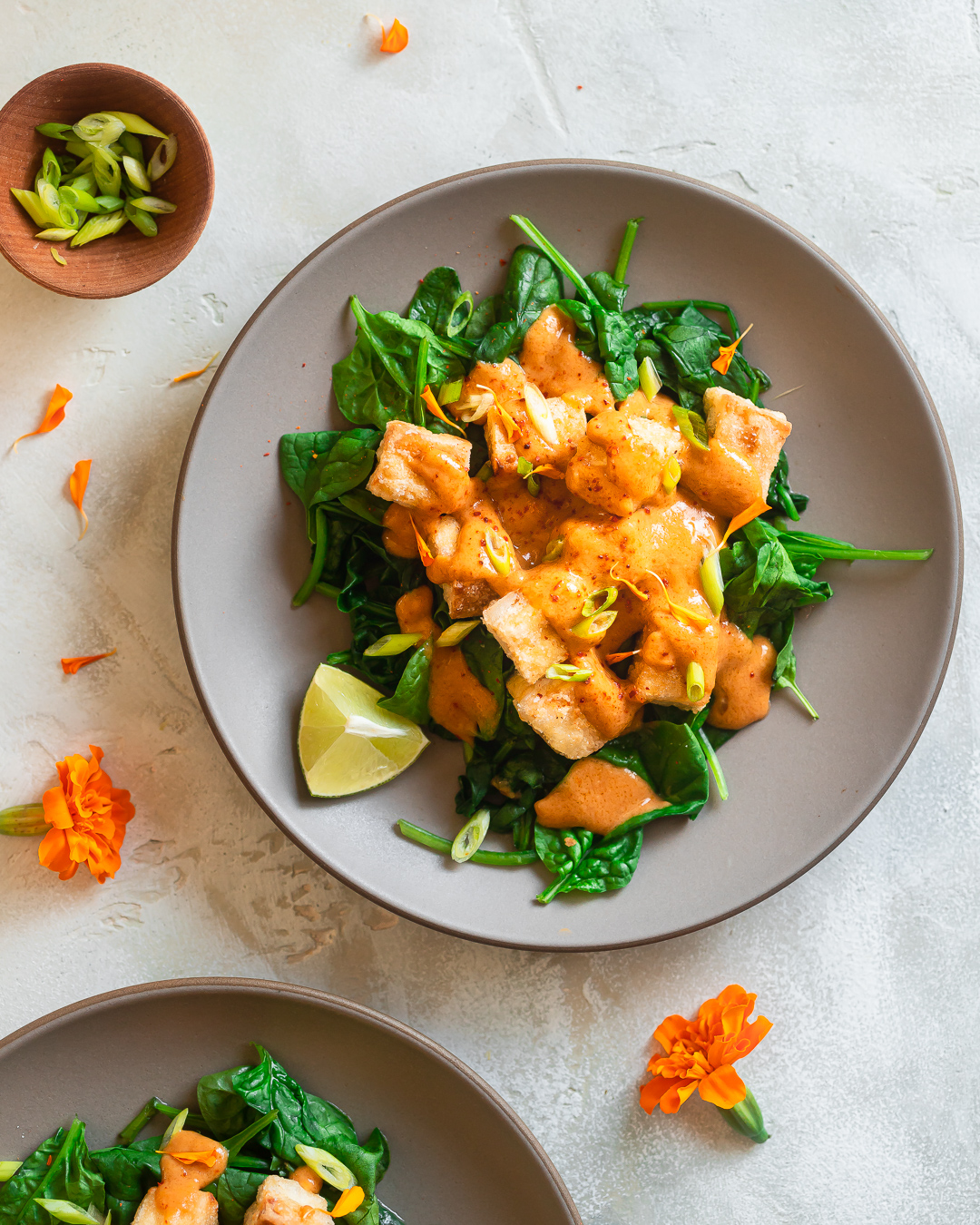 overhead shot of a serving of Thai Tofu with Peanut Sauce served over sauteed spinach