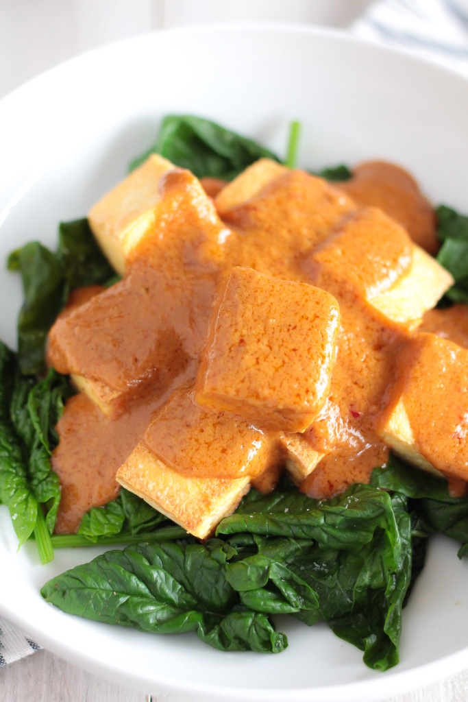 close-up of a bowl of Vegan Thai Tofu with Peanut Sauce served over spinach