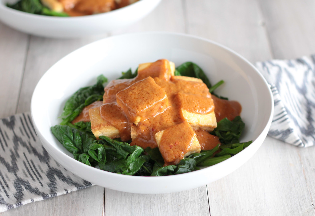 side view of a bowl of Thai Tofu with Peanut Sauce served over spinach