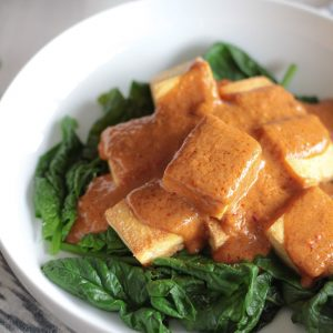 Vegan Thai Tofu with Peanut Sauce served on steamed spinach