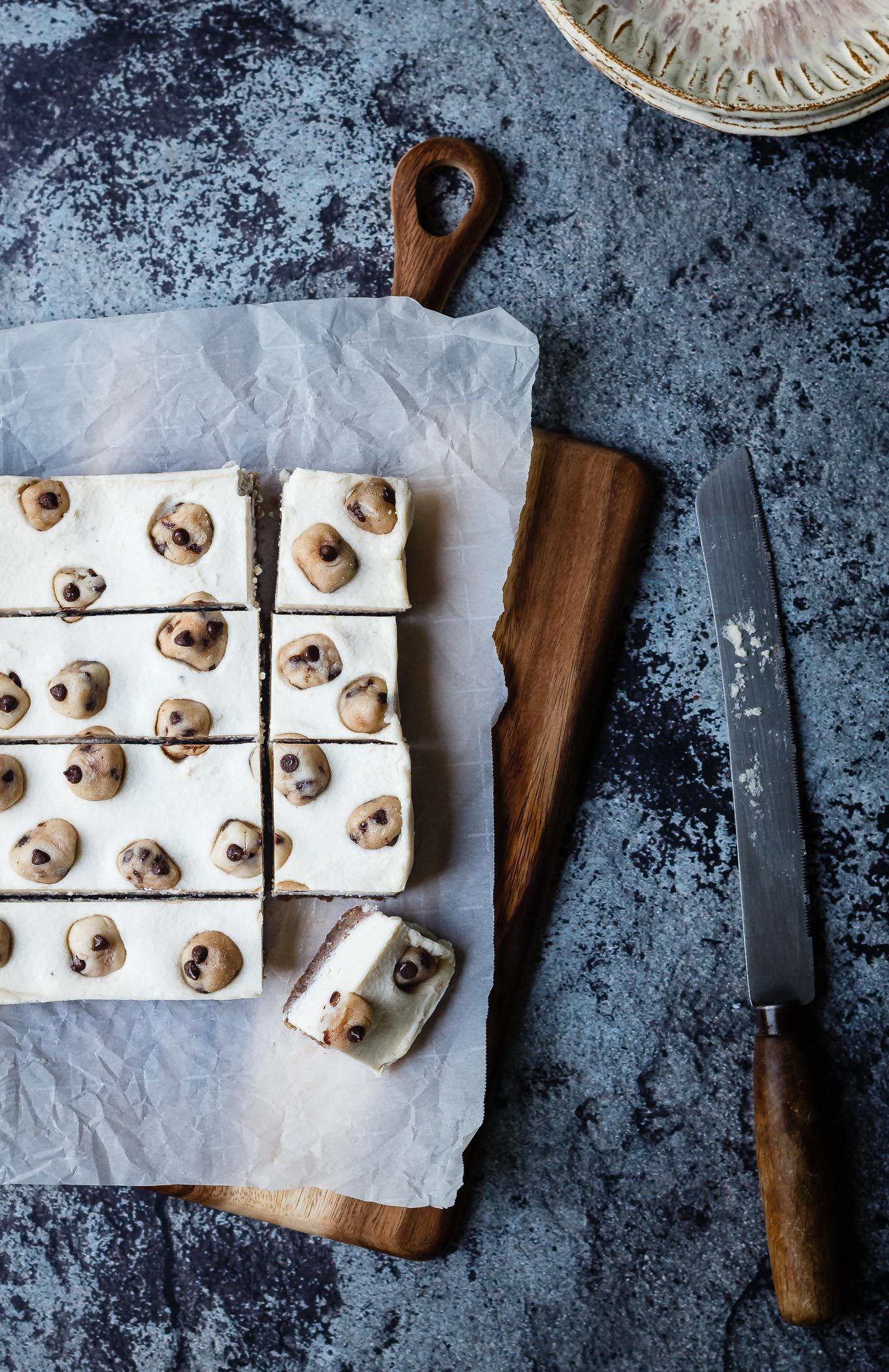 partially cut Vegan Cookie Dough Cheesecake Bars on a cutting board