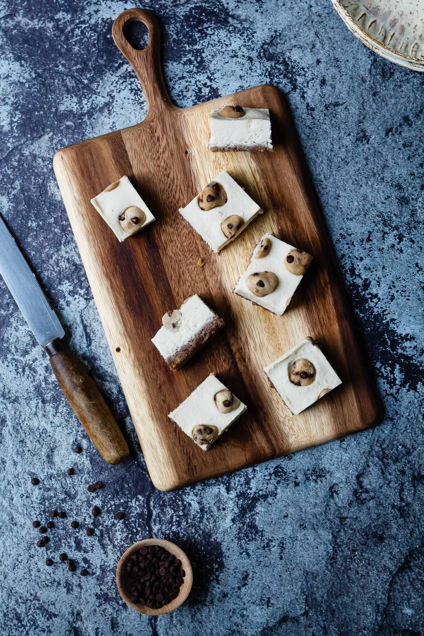 Vegan Cookie Dough Cheesecake Bars on a cutting board with knife