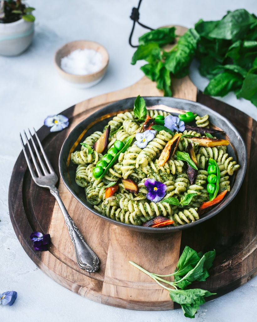 a bowl of pea pesto rotini on a round wooden cutting board